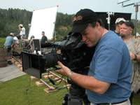 Really good looking cameraman Filming on Set with large video camera