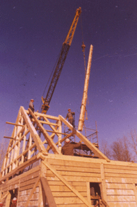 construction of a building at fort william historical park with a crane and raw timbers