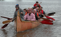 Group paddling canoe ion modern and historic costumes