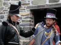 Voyageur held at sword point by a soldier