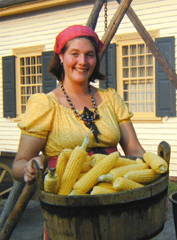 Female reinactor holding large cauldron of corn