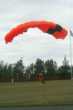 Red parachute jumper landing