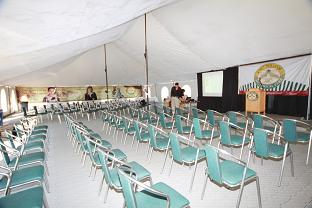 Dozens of chairs and podium setup inside the tent