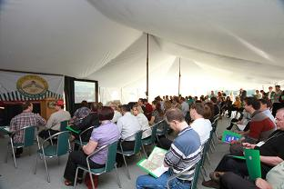 Tent full of attendees sitting in the conference tent