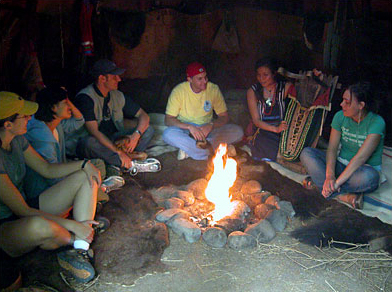 Group sitting around fire in wigwam