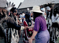 Anishnawbe Men in Regalia greets a lady with a handshake