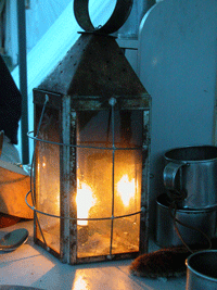 Tin lantern with burning candle close up in a dusk setting