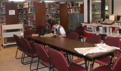 man sitting at study table in library with books in background