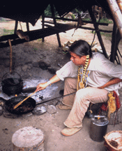 Ojibwe man cooking over fire.png