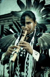 Native man in regalia playing traditional flute.png