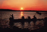Silhouette of Voyageurs Paddling Canoe at sunset