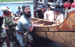 Voyageurs carrying birch bark canoe out of water