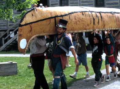 voyageur and guests carry a large birch bark canoe on their shoulders