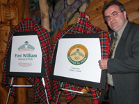 General Manager standing next to new FWHP Logos for 2003 anniversart