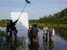 Group of voyageurs standing in river with film crew with a large sun reflector