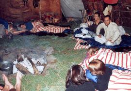 Visitors sleeping inside wigwam on a floor covered in pine boughs and historic red striped blankets
